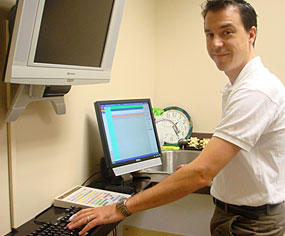 Chiropractor Edward Beck reviews patient history at the computer.