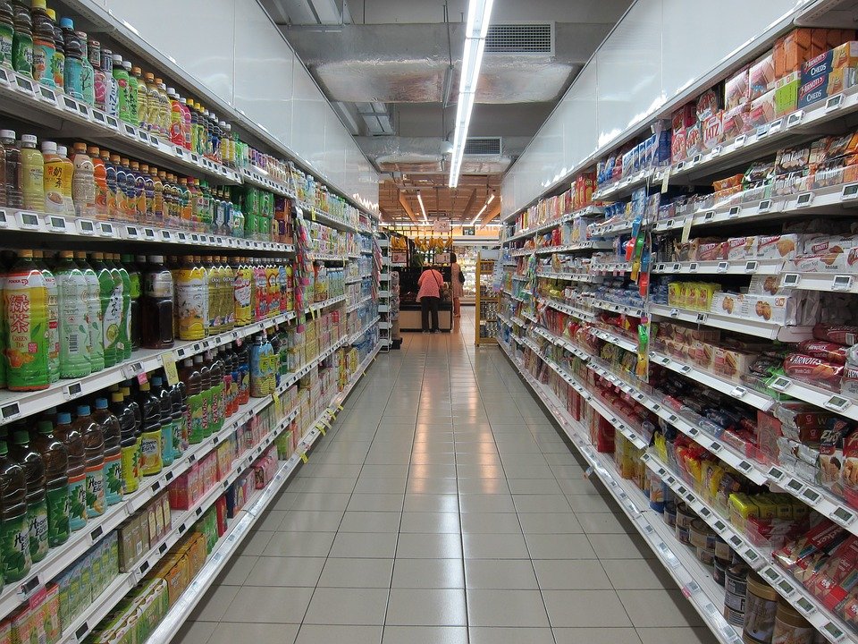 Grocery store aisle of soda and snacks.