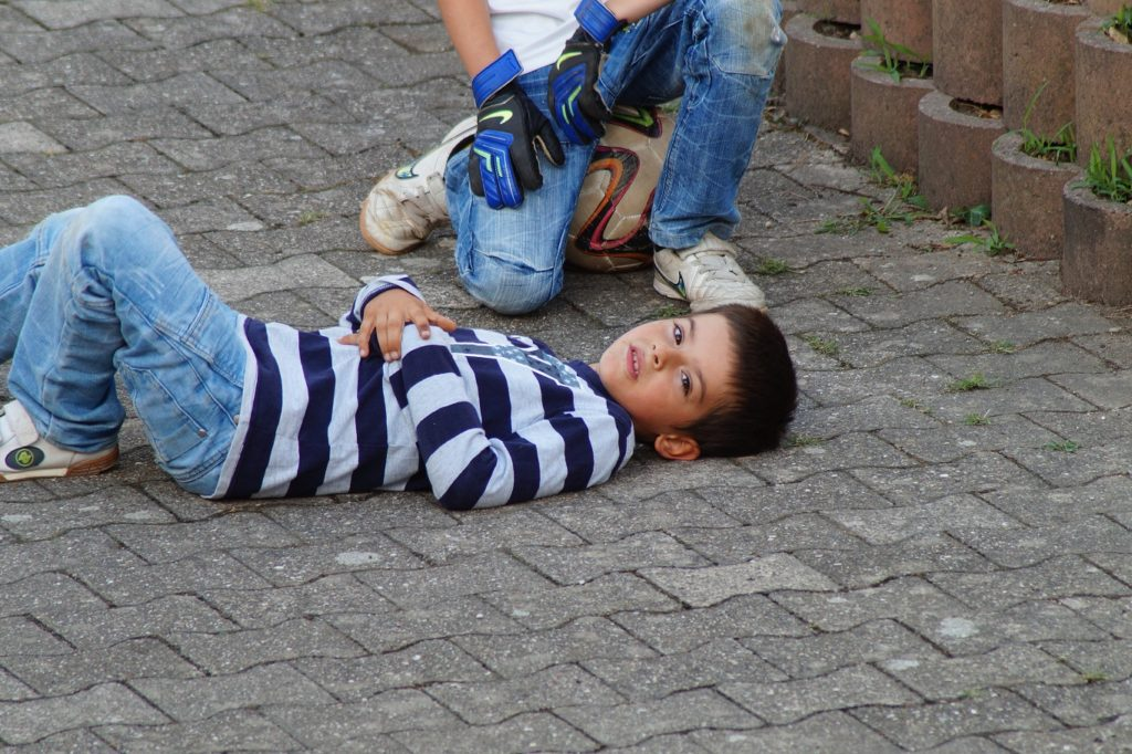 child lying on the street with soccer ball