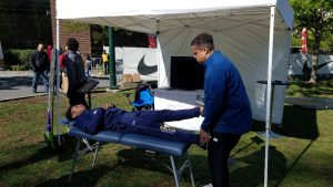 Athlete at Penn Relays getting treated by Dr. Booker